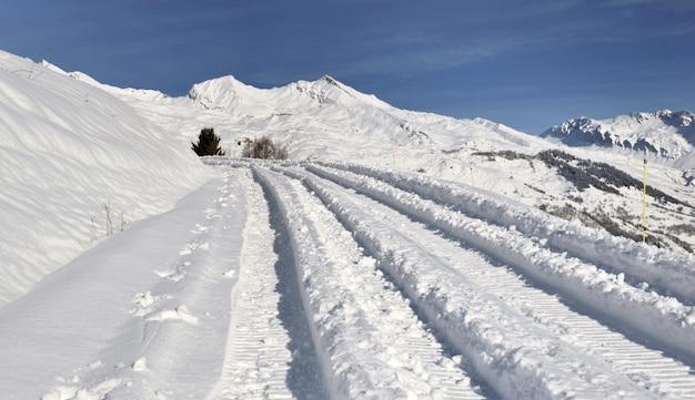 Trilhas de carro na neve cobriram uma estrada na montanha alpina no inverno
