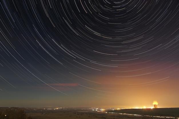 Trilhas de estrelas no céu noturno. uma visão do espaço estrelado no fundo da iluminação da cidade.