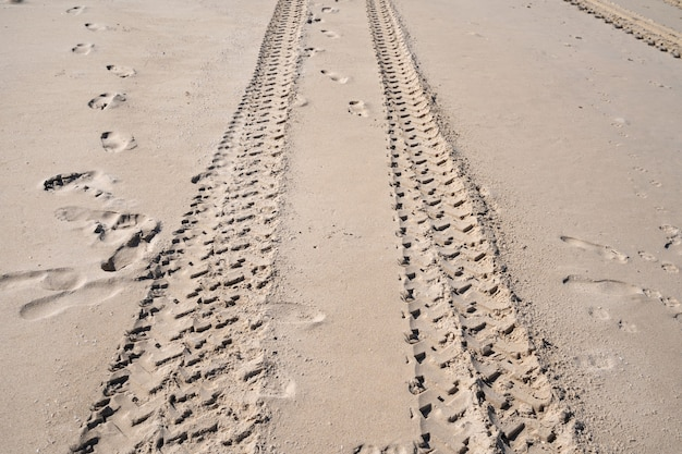 Trilhas de pneus 4x4 se cruzando trilhas de pneus no fundo de textura de areia.