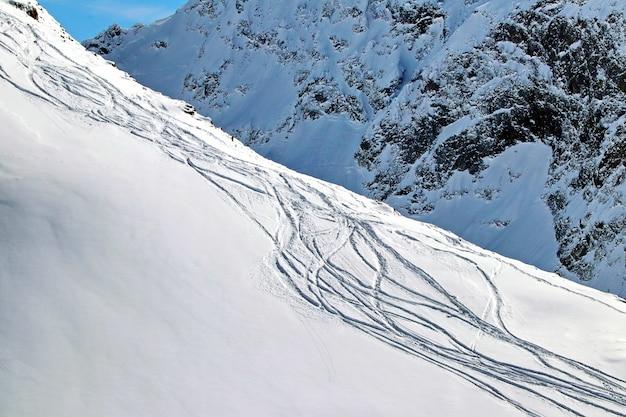 Trilhas de snowboard em uma montanha nevada em um dia ensolarado
