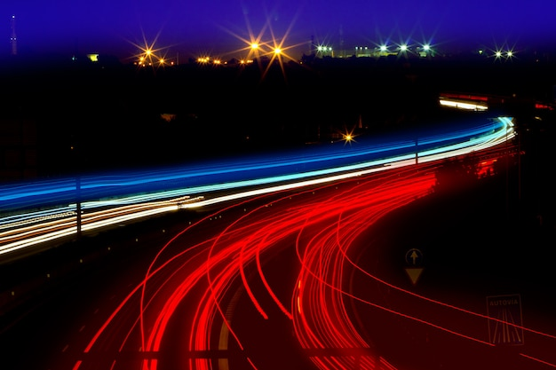 Trilhas leves de carro em vermelho e branco na estrada à noite