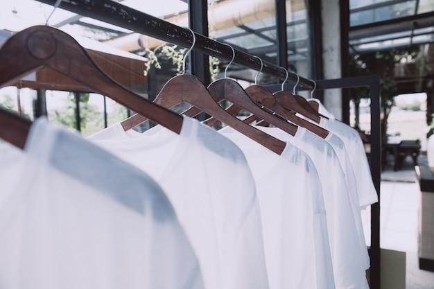 Trilho com camisetas brancas em cabides na loja. panos de verão casuais