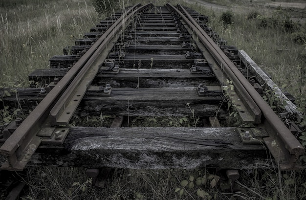 Trilho de trem velho no meio de um campo