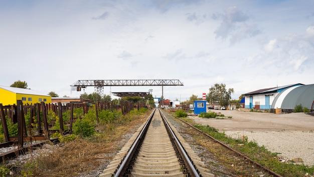 Trilhos de trem de grande plano contra o de um canteiro de obras, oficina de produção, armazém, guindaste de pórtico.