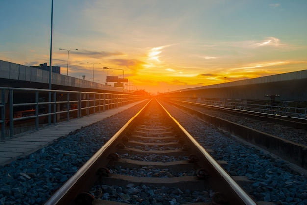 Trilhos de trem e a luz laranja do pôr do sol
