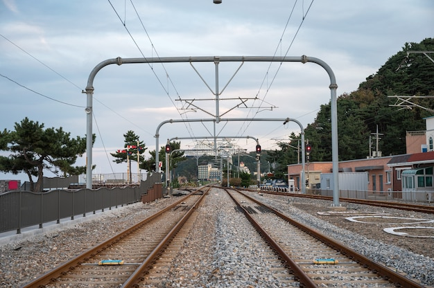 Trilhos de trem e poste elétrico na estação