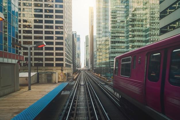 Trilhos de trem elevados estão correndo acima da linha férrea entre o edifício na linha loop