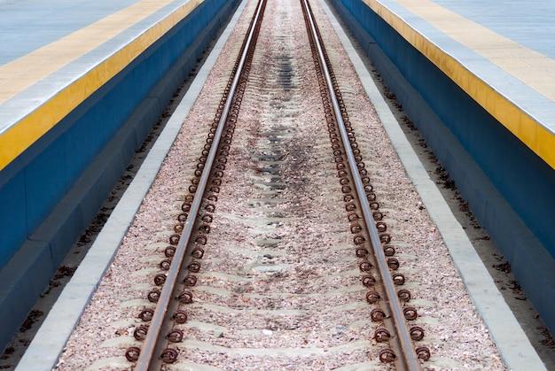 Trilhos de trem em linha reta e longa no meio da foto.