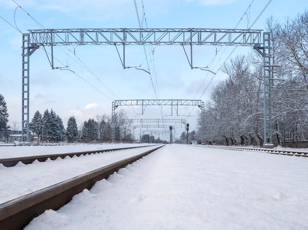 Trilhos vazios entre os montes de neve de inverno branco, ferrovia rural.