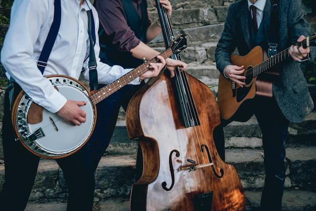 Trio de músicos com violão, banjo e contrabaixo