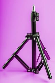 Tripé em fundo rosa para câmera de foto-vídeo e flash. espaço livre