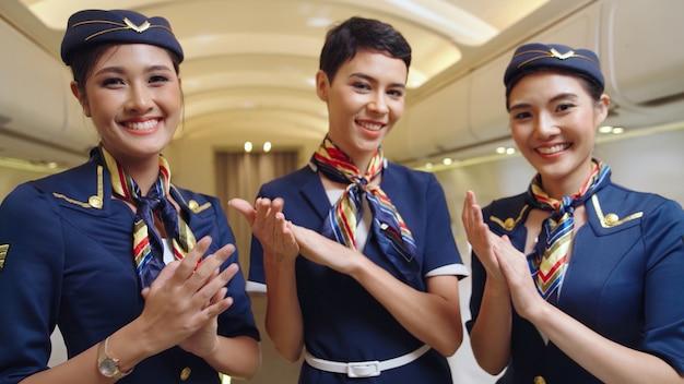 Tripulação de cabine batendo palmas no avião. transporte de linha aérea e conceito de turismo.
