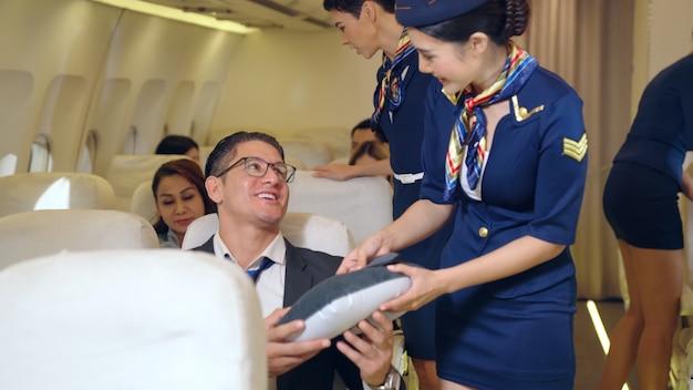 Tripulação de cabine dando travesseiro a um passageiro