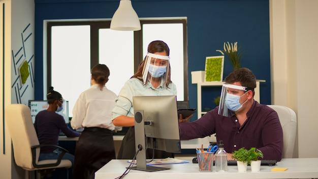 Tripulação de empresários trabalhando em um novo projeto de inicialização em loft moderno, usando viseira e máscara protetora. grupo multiétnico conversando, consultando-se mutuamente em um novo local de trabalho normal, respeitando a distância social