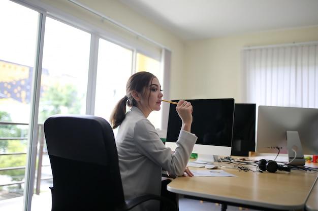 Tripulação de jovem empresária inteligente trabalhando com novo projeto de inicialização no escritório loft moderno