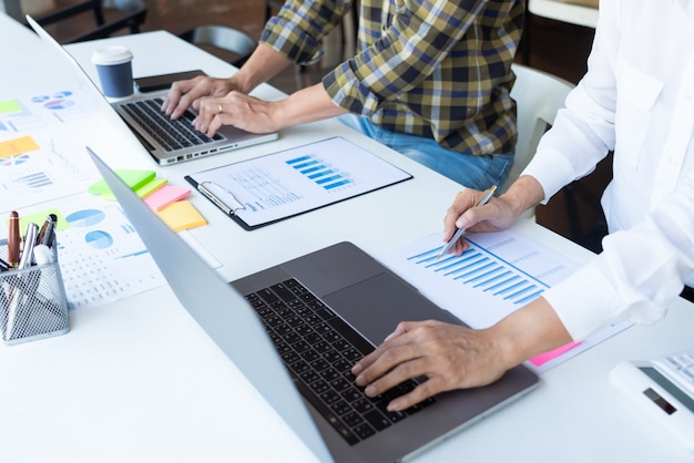 Tripulação de jovens gerentes de negócios trabalhando com novo projeto de inicialização, trabalhando com plano na mesa de escritório e computador digital moderno.