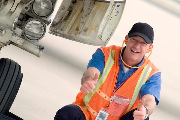 Tripulação de terra de aeroporto sorrindo, close-up, retrato