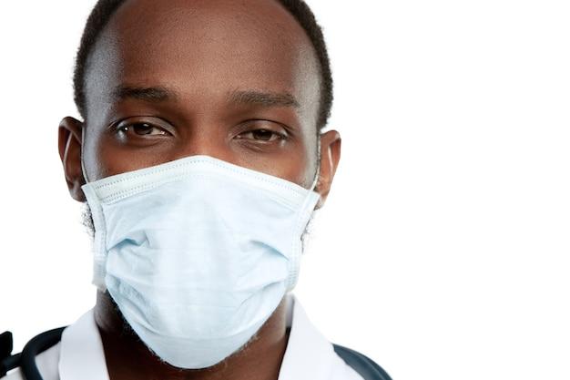 Triste, cansado, desespero. jovem médico com estetoscópio e máscara facial em fundo branco do estúdio. parece triste, sério. conceito de saúde e medicina, pandemia de coronavírus, epidemia de perigo, covid.