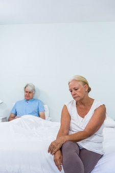 Triste casal sênior sentado na cama