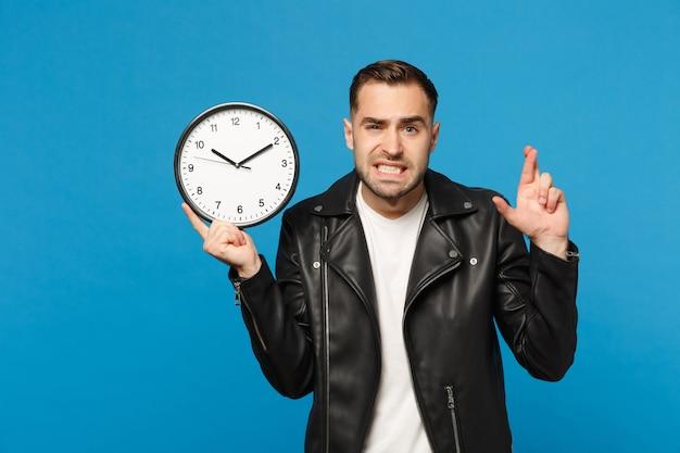 Triste chateado elegante jovem com barba por fazer na jaqueta de couro preta, camiseta branca, segurando o relógio redondo isolado no retrato de estúdio de fundo de parede azul. conceito de estilo de vida de pessoas. se apresse. simule o espaço da cópia.