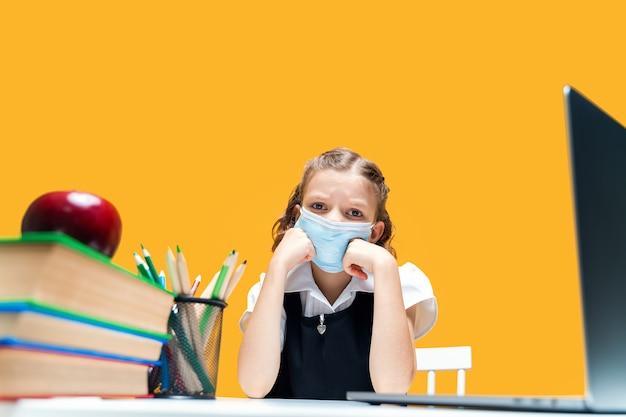 Triste colegial caucasiana usando máscara médica e estudando em casa com laptop de ensino à distância