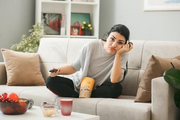 Triste, colocando a mão na bochecha, jovem segurando o controle remoto da tv com biscoito, sentada no sofá atrás da mesa de centro na sala de estar