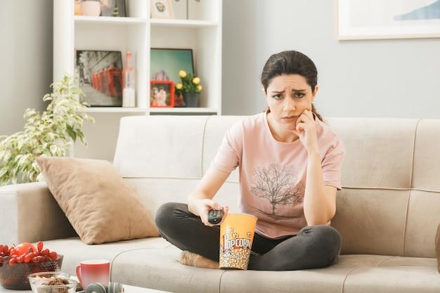Triste, colocando a mão na bochecha, jovem segurando o controle remoto da tv, sentada no sofá atrás da mesa de centro na sala de estar