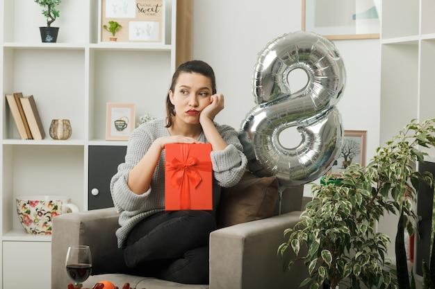 Triste, colocando a mão na bochecha linda garota feliz dia da mulher segurando um presente sentado na poltrona na sala de estar