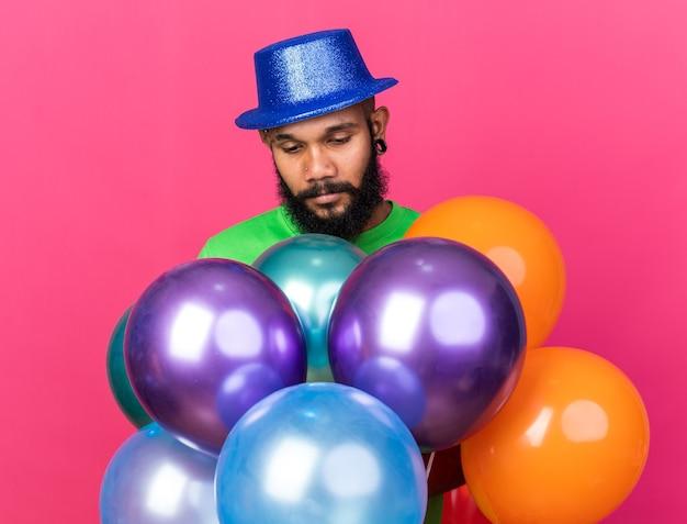 Triste com o jovem afro-americano de cabeça baixa usando chapéu de festa atrás de balões