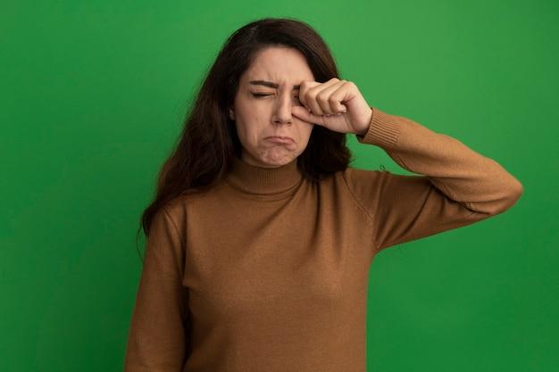 Triste, com os olhos fechados, bela jovem enxugando o olho com a mão isolada na parede verde