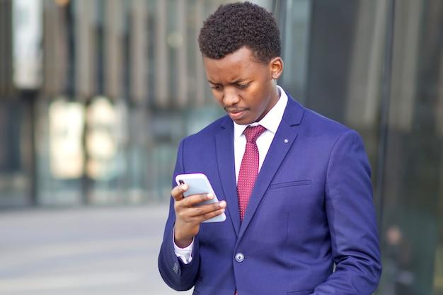 Triste concentrado chateado frustrado afro-americano negro homem olhando para a tela de seu smartphone. trabalhador de escritório infeliz, empresário em traje formal ao ar livre. problemas com celular.