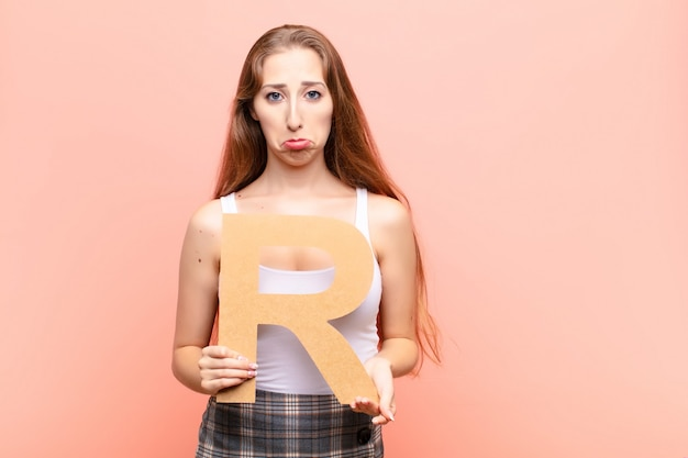 Triste, deprimido, infeliz, segurando a letra r do alfabeto para formar uma palavra ou frase.