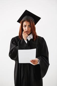 Triste descontente feminino africano graduado segurando o teste.