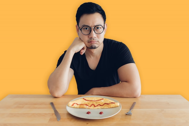 Triste e chato homem asiático está comendo café da manhã caseiro conjunto de omelete.
