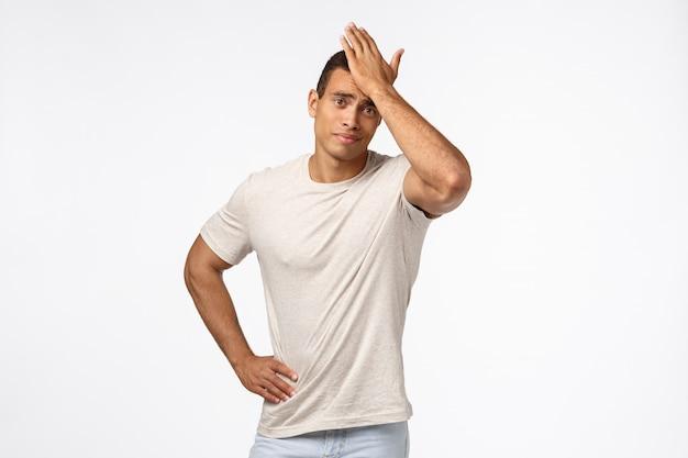 Triste e desapontado cara bonito sombrio de camiseta casual, soco na testa, movimento facial, sorriso desagradável, alguém o decepcionou, esqueceu-se de uma tarefa importante, ficou frustrado