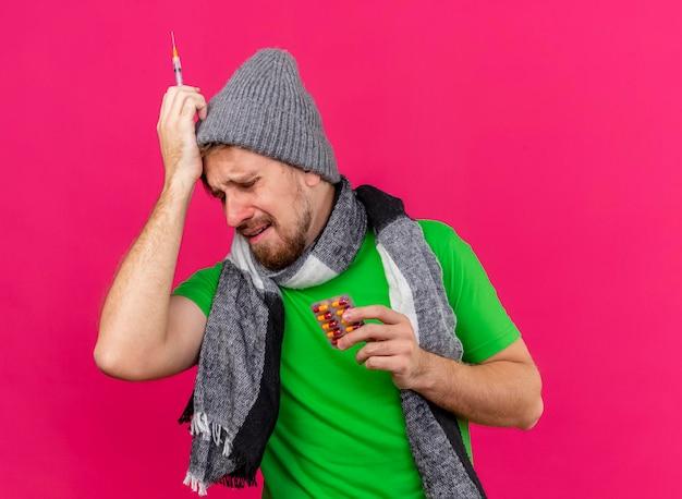 Triste e dolorido jovem eslavo doente usando chapéu de inverno e lenço segurando uma seringa e um pacote de cápsulas tocando a cabeça com os olhos fechados, isolado na parede rosa com espaço de cópia