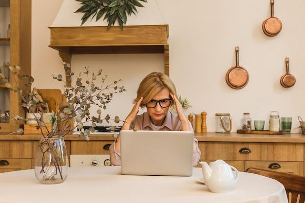 Triste e frustrada aposentada sênior com olhar deprimido, segurando a mão no rosto dela, calculando o orçamento familiar, sentado no balcão da cozinha com o laptop, café.