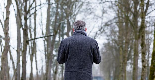 Triste e solitário homem andando na paisagem de inverno
