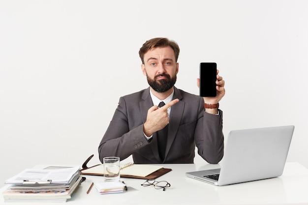 Triste empresário barbudo atraente, gerente sênior sentado na área de trabalho, olhando para a câmera com expressão facial taciturna, vestido com um terno caro com gravata, apontando com o dedo para seu dispositivo.