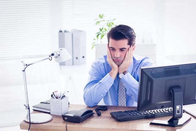 Triste empresário sentado em sua mesa