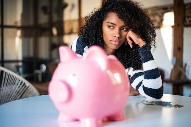 Triste frustrada mulher negra com mealheiro