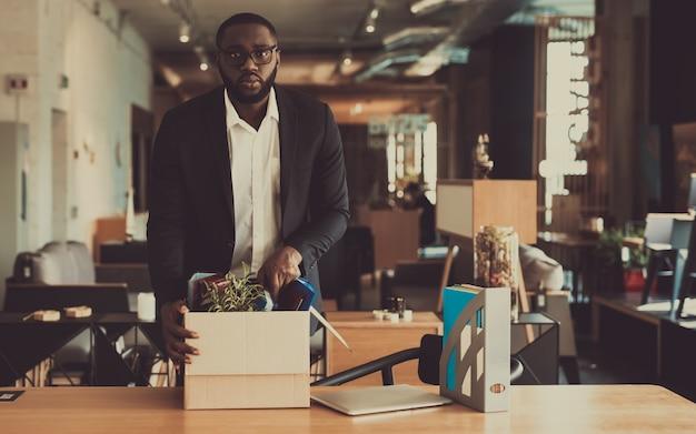 Triste gerente preto deixa o local de trabalho com caixa de escritório.
