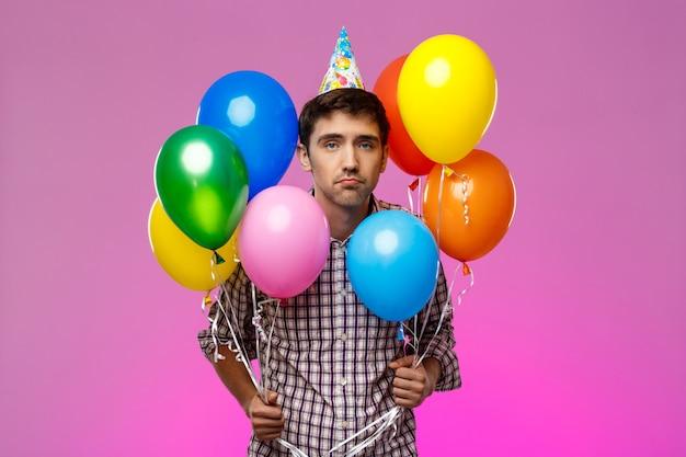 Triste homem comemorando aniversário, segurando balões coloridos sobre parede roxa.