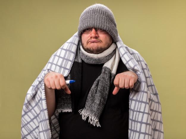 Triste homem de meia-idade doente usando chapéu de inverno e lenço enrolado em um termômetro segurando uma manta