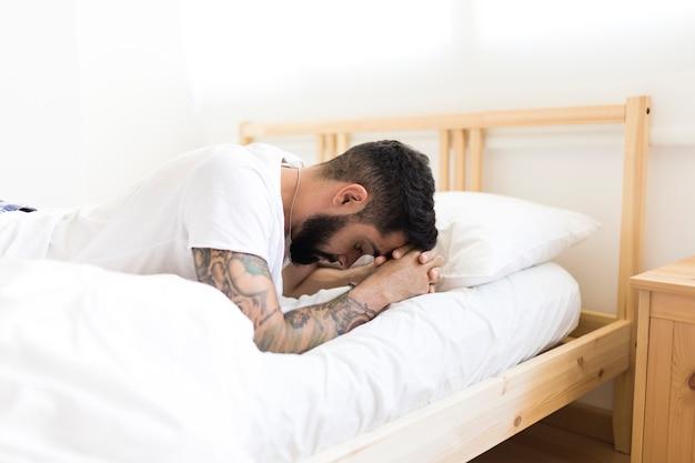 Triste homem deitado na cama no quarto