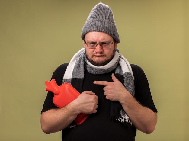 Triste homem doente de meia-idade usando chapéu de inverno e lenço segurando e apontando para uma bolsa de água quente isolada na parede verde oliva