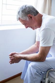 Triste homem idoso sentado na cama