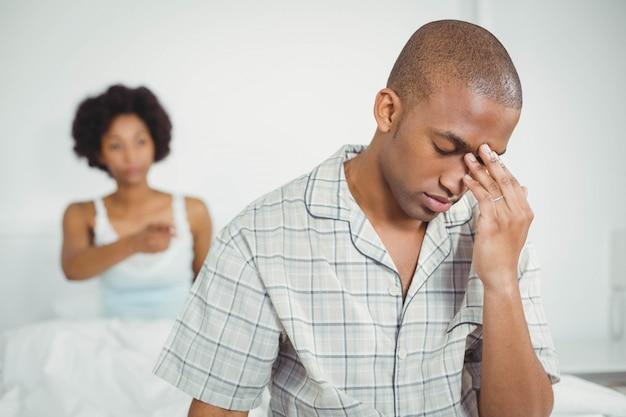 Triste homem sentado na cama depois de discutir com sua namorada