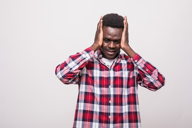 Triste, infeliz estudante do sexo masculino, de pele escura, apertando a cabeça com as mãos, contorcendo-se de dor, sofrendo de dor de cabeça depois de passar uma noite sem dormir se preparando para os exames. pessoas, estresse, tensão e enxaqueca