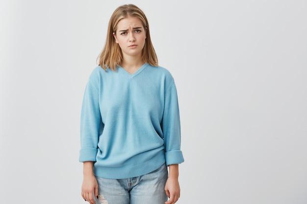 Triste, infeliz, linda mulher com cabelos lisos lisos, com olhos escuros e encantadores, posando no estúdio, chateada por causa de más notícias. menina bonita de jeans e suéter azul.